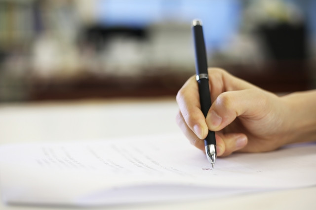 ボールペンを持ち書類に記載する右手
