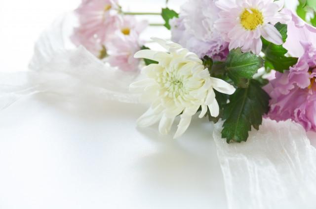 白いシーツの上に置かれた白とピンクの花々