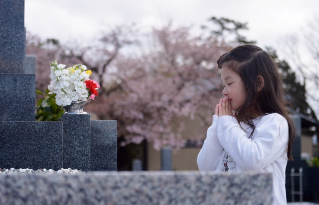 お墓の前で手を合わせ目を閉じる少女
