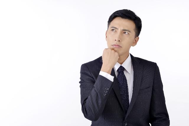 右こぶしを顎にあて考える男性